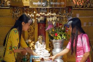 Junge Burmesinnen waschen den Buddha, der dem Wochentag ihres Geburtstages zugeordnet ist. Sule Pagode. Yangon. Rangun. Myanmar