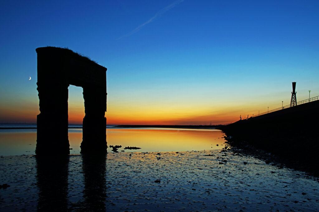 Nordsee Sonnenuntergang am alten Fähranleger in Eckwarderhörne mit dem Leuchtfeuer Preußeneck im Hintergrund blaue Stunde