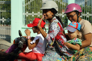 Verkehr Traffic in Myanmar / Mandalay. Strahlen auf dem Motorrad / Moped.