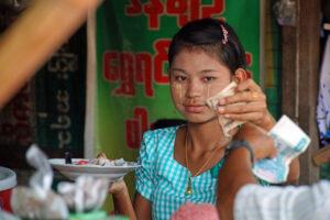 Lokaler Markt am Stadtrand von Yangon. Burma / Myanmar. Junge Burmesin mit Thanaka im Gesicht.